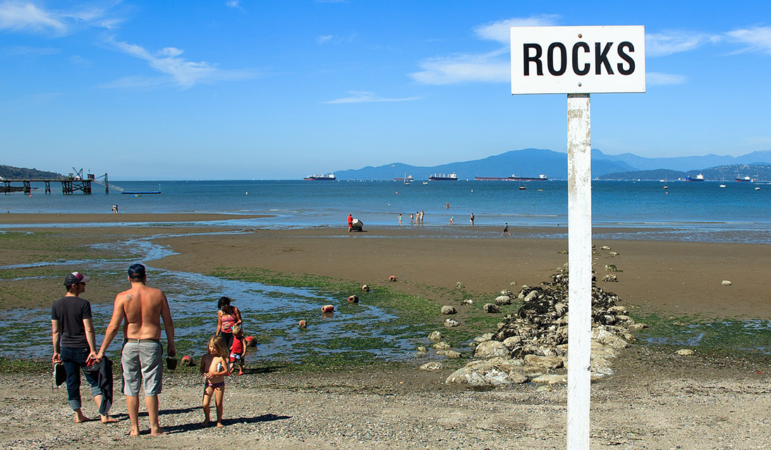 low tide, bathers, sign warning about