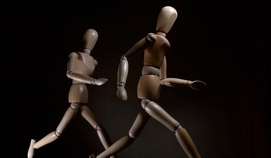 naked wooden dolls running